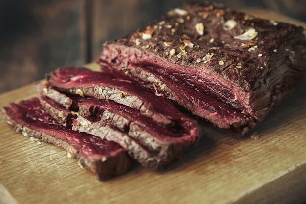 Close up foco carne grelhada em fatias finas na placa de madeira