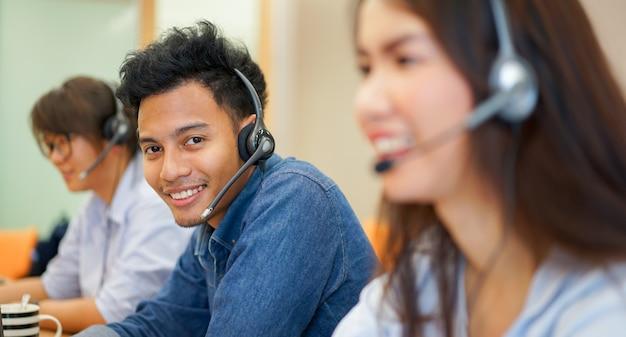 Close-up foco no homem asiático de call center com o trabalho da equipe