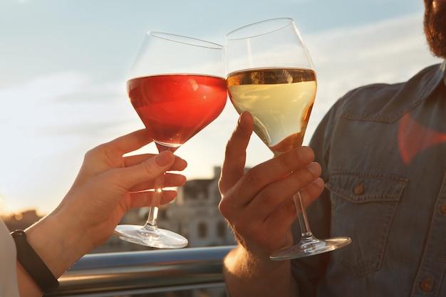 Close-up foto cortada de um casal apaixonado tilintando taças de vinho no pôr do sol ao ar livre