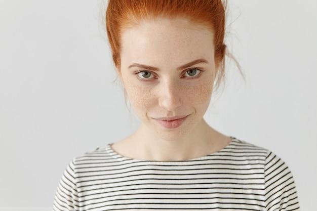 Close-up foto da bela jovem e atraente modelo feminino caucasiano com olhos verdes e sardas