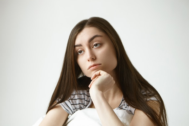 Close-up foto da infeliz jovem morena linda europeia na casa dos vinte anos tocando o queixo, com expressão facial indiferente, sentindo-se entediada, passando o fim de semana em casa, sem fazer nada