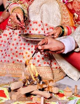 Close-up foto da noiva e do noivo realizando rituais religiosos