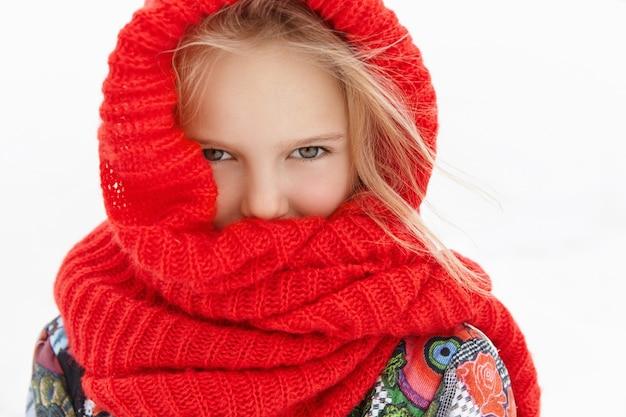Close-up foto de adorável criança feminina sentindo frio enquanto caminha ao ar livre