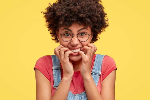 Close-up foto de desesperada irritada furiosa mulher afro-americana morde as unhas, tem uma expressão irritada e nervosa, reage a notícias negativas, vestida casualmente, isolada sobre uma parede amarela