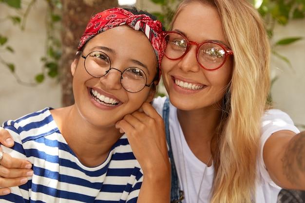 Close-up, foto de duas garotas amigáveis mestiços posando para selfie, demonstrando amizade inter-racial