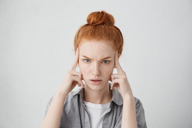 Close-up foto de estressada jovem caucasiana infeliz usando seu cabelo ruivo em um coque, mantendo os dedos nas têmporas, sofrendo de forte dor de cabeça, enxaqueca ou tentando se lembrar de algo