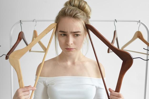 Close-up foto de estressada linda jovem usando a blusa branca de ombros abertos segurando duas prateleiras vazias na frente do rosto e franzindo a testa, com olhar pensativo perplexo, pensando no que colocar para trabalhar