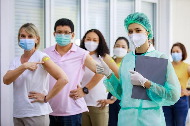 Close-up, foto de estúdio de uma jovem enfermeira com luvas de borracha e uniforme de proteção total, segurar a placa de informações mostrar o polegar para animar o grupo de pacientes étnicos multinacionais na linha vacinada.