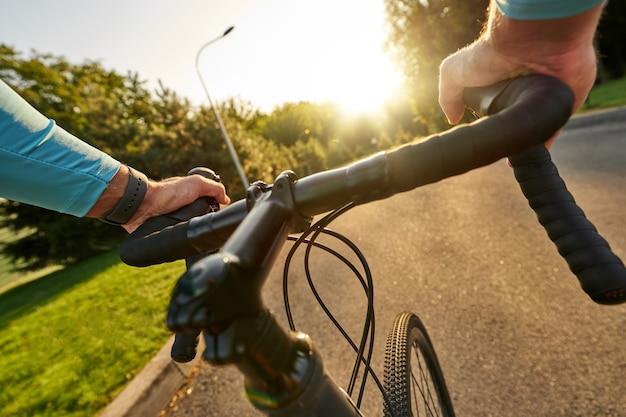 Close-up foto de mãos no guiador de ciclista profissional andando em sua bicicleta de estrada