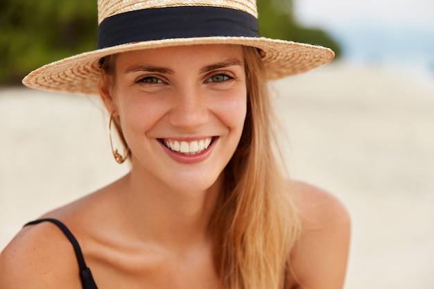 Close-up foto de mulher atraente tem olhos calorosos, sorriso largo com dentes brancos e regulares, usa chapéu de praia, recrie em resort luxuoso. conceito de viagens e turismo de verão. mulher em ilha tropical