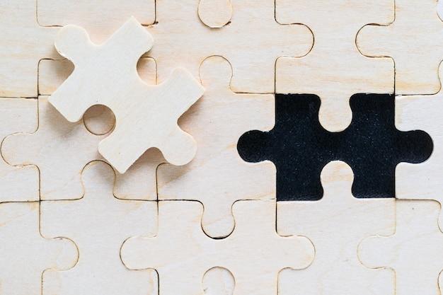 Close-up foto de peças de quebra-cabeça de madeira em fundo preto, conceito de negócio