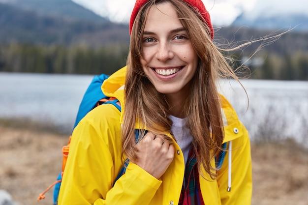 Close-up foto de sorridente turista feminina atraente com casaco amarelo, carrega mochila