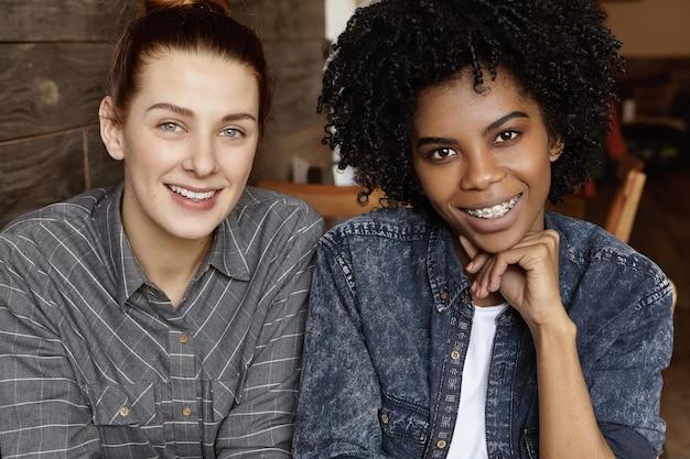 Close-up foto de um casal de lésbicas feliz descansando em um restaurante aconchegante