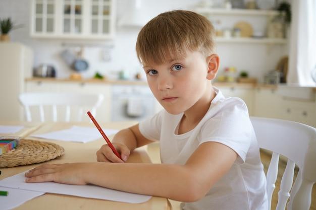 Close-up foto de um estudante europeu em uma camiseta branca sentado à mesa de madeira desenhando ou fazendo lição de casa com o interior da cozinha, olhando, com expressão facial séria