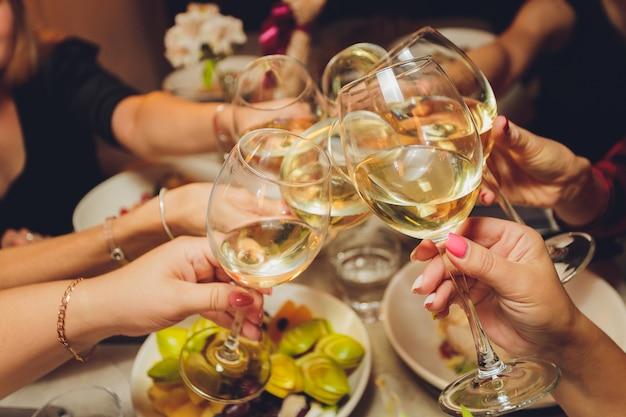 Close-up foto de um grupo de pessoas tilintando taças com vinho ou champanhe na frente do bokeh