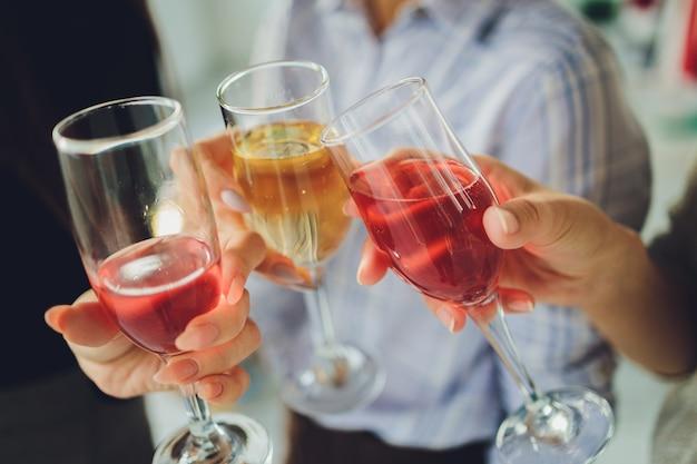Close-up foto de um grupo de pessoas tilintando taças com vinho