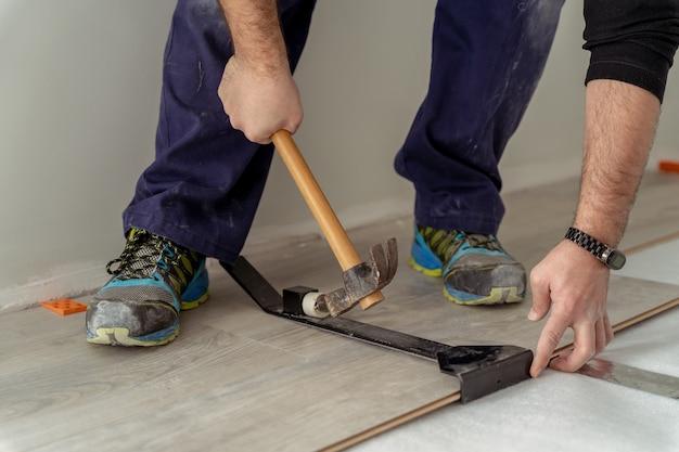 Close-up, foto de um trabalhador montando piso laminado