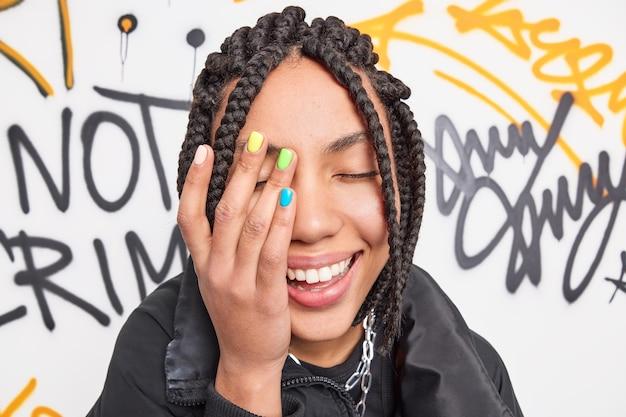 Close-up foto de uma adolescente feliz fazendo o rosto com a palma da mão sorrisos amplamente com manicure colorida e dreadlocks expressam poses de emoções positivas contra parede de graffiti desenhada vestida com roupas da moda