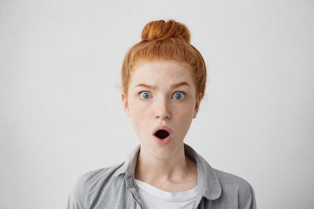 Close-up foto de uma adolescente sardenta espantada usando seu cabelo ruivo em um coque, levantando as sobrancelhas e abrindo a boca com um olhar assustado, absolutamente chocada