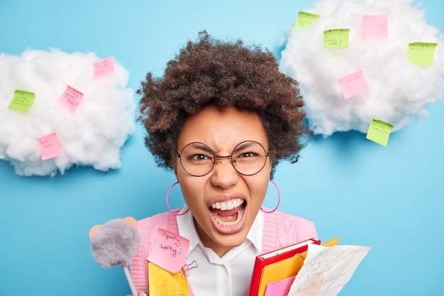Close-up foto de uma aluna emocional irritada com cabelos cacheados gritando alto e irritada com o estudo constante cercada por notas isoladas sobre a parede azul