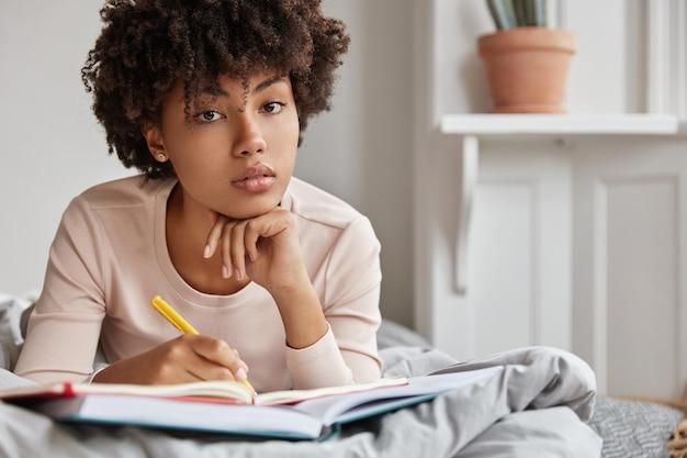 Close-up foto de uma estudante universitária séria de pele escura fazendo tarefas em casa na cama, escrevendo no caderno com uma caneta e mantendo a mão sob o queixo