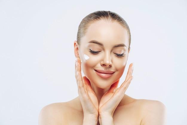 Close-up foto de uma jovem adulta com ombros nus aplica creme hidratante nutritivo para pele macia e pura, tem expressão terna, isolada na parede branca. beleza, conceito de cosmetologia