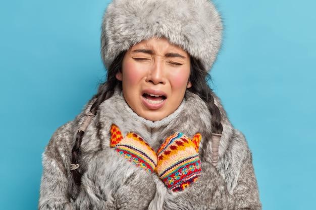 Close-up foto de uma jovem inuit asiática descontente usando luvas de tricô e roupa de inverno parece fria durante o inverno gelado isolada sobre a parede azul