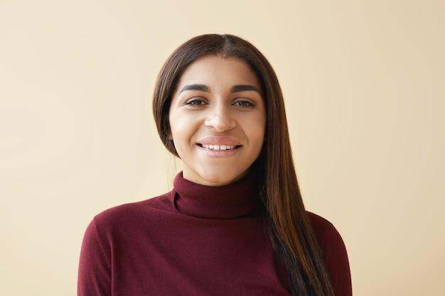 Close-up foto de uma jovem mulher afro-americana simpática e elegante com cabelo liso escuro e liso, posando de olhar alegre e feliz