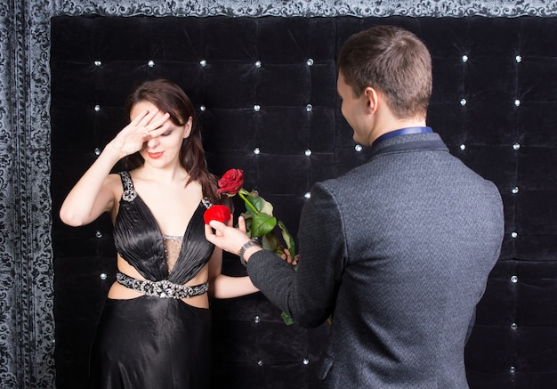 Close up, foto de uma jovem oprimida em um elegante vestido preto recebendo uma rosa vermelha e uma caixa de joias vermelha de seu namorado feliz