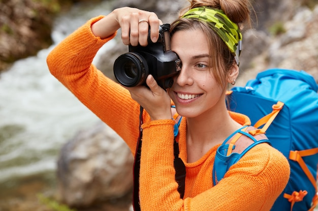 Close-up foto de uma jovem turista caucasiana feliz vestida com um macacão laranja brilhante