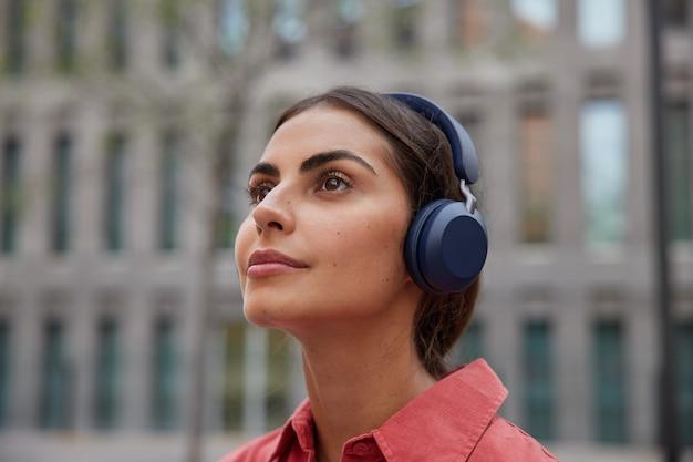 Close-up foto de uma modelo feminina morena pensativa ouve música da lista de reprodução usa fones de ouvido sem fio anda fora durante o dia pensa em algo descobre uma nova cidade e locais de interesse