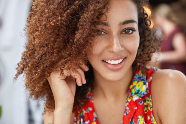 Close-up foto de uma mulher afro-americana de aparência agradável e alegre com uma expressão alegre, vestida com roupas de verão brilhantes