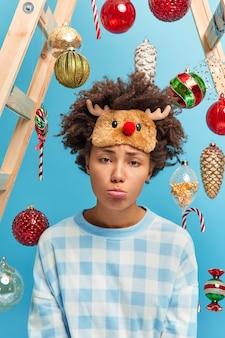 Close-up foto de uma mulher afro-americana descontente com uma expressão sombria no rosto para a câmera triste por estar doente durante as férias de inverno usa uma máscara de dormir quente e um pijama decora a casa com árvores de ano novo