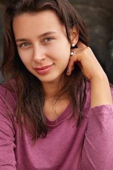Close-up foto de uma mulher atraente com cabelo escuro, olhos verdes, lábios grandes, olhar direto