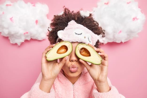 Close-up foto de uma mulher de cabelo encaracolado cobre os olhos com metades da dobra de abacate. lábios se preocupa com a tez da pele, usa uma máscara de dormir macia e um pijama isolado sobre a parede rosa