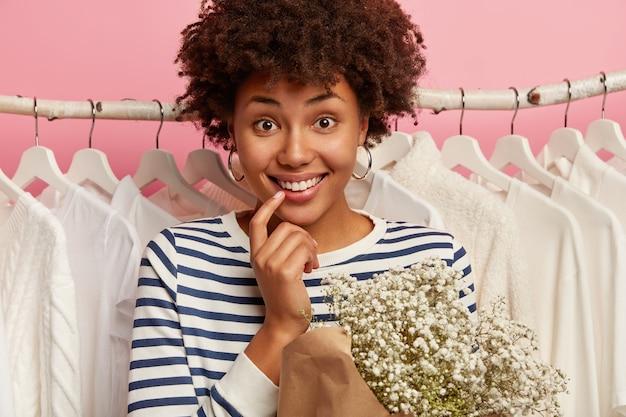 Close-up foto de uma mulher de cabelo encaracolado feliz em pé perto de roupas brancas nos corredores da loja, vestida com um macacão listrado de marinheiro, segurando um lindo buquê