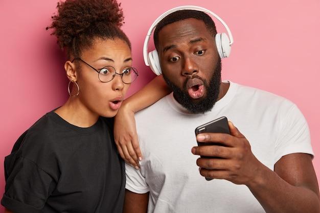 Close-up foto de uma mulher de pele escura, homem assiste o vídeo online com expressões chocadas olhando para a tela do smartphone, tem uma reação surpresa em algo vestido casualmente, posar perto de um do outro