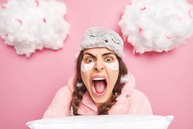 Close-up foto de uma mulher morena emocionada gritando alto mantendo a boca bem aberta vestida de pijama