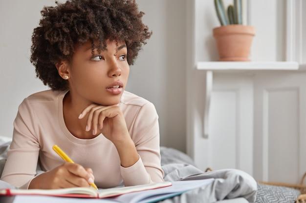 Close-up foto de uma senhora de pele escura pensativa com corte de cabelo afro, mantém a mão sob o queixo, anota o texto no bloco de notas com caneta amarela, usa roupas casuais, deita-se em uma cama confortável, focado à parte. conceito de descanso