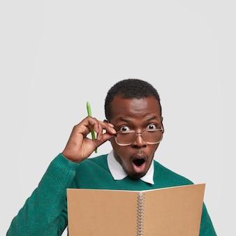 Close-up foto do jovem empresário com pele escura, mantém os olhos arregalados, mão na borda dos óculos, abre a boca em surpresa