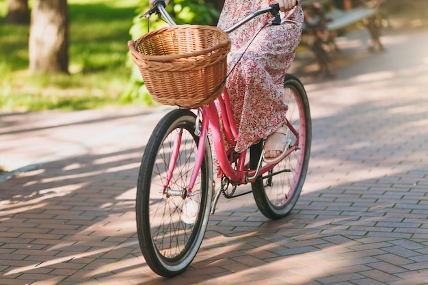 Close-up foto recortada de jovem em vestido floral rosa longo andando em bicicleta vintage com cesta para compras, comida ou flores ao ar livre, rodas, tempo de recreação feminino na primavera ou parque de verão.