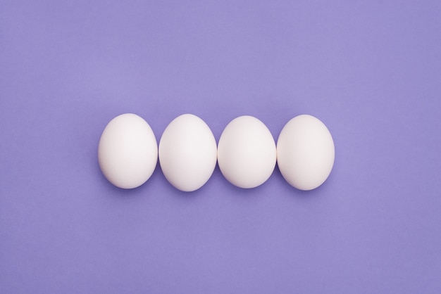 Close-up foto vista superior de quatro ovos em fileira com fundo de cor violeta isolado de casca branca