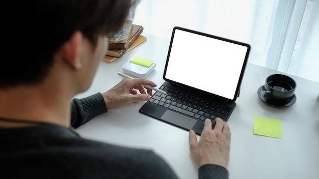 Close-up freelancer de homem vista trabalhando no tablet do computador em casa.