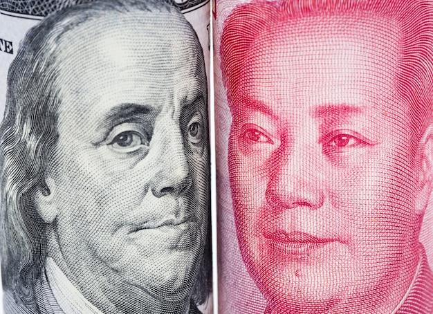 Close up frente a frente de benjamin franklin e de mao tse tung das cédulas do dólar americano e do yuan de china.