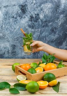 Close-up frutas cítricas em caixa de madeira com bebida fermentada
