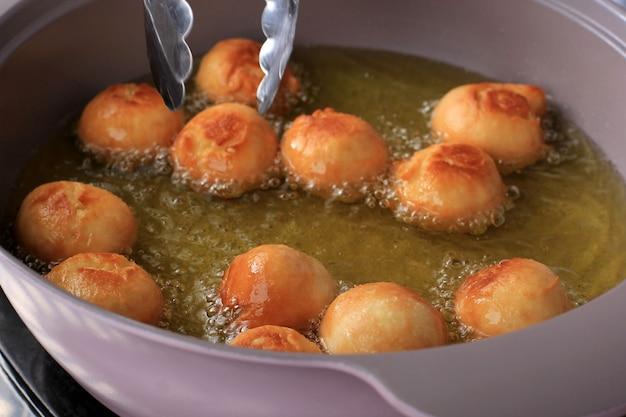 Close up frying odading (kue bantal), comida de rua viral da indonésia, feita de farinha, fermento e açúcar.