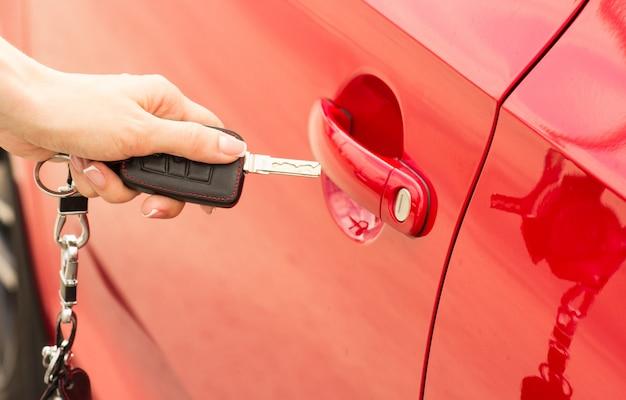 Close-up, garota abre o carro da porta pela chave