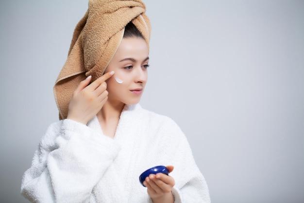 Close-up garota coloca um creme para o rosto