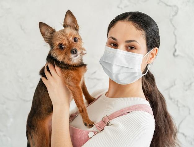 Close-up garota com máscara segurando cachorro