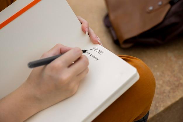 Close-up garota escrevendo no diário